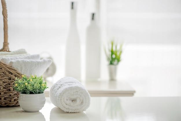 白いタオル、白いテーブル、コピースペース、ぼやけたバスルームの背景。 Premium写真