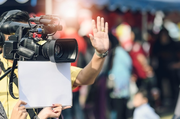 Оператор и помощник снимают сцену фильма с камерой Premium Фотографии