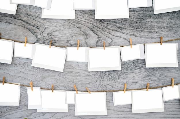 クリッピングパスと木製の背景に物干し用ロープにぶら下がっている空白の紙の写真フレーム。 Premium写真