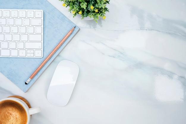 大理石のテーブルの上の白いキーボード。 Premium写真
