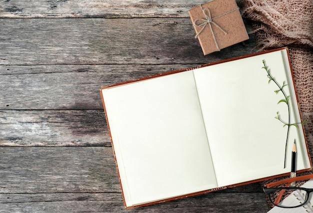 トップビューで木製のテーブルに開いているノートブックをモックアップします。 Premium写真