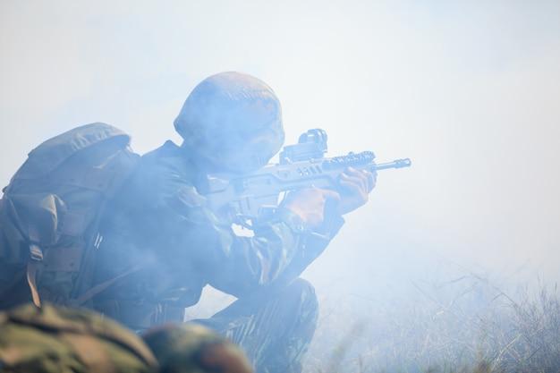完全に制服を着た銃を保持しているタイの兵士と森林の山での完全な訓練の実行 Premium写真