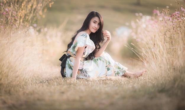 美しいアジアの女性女の子座って公園フラワーピクチャースタイルヴィンテージでポーズをとる Premium写真
