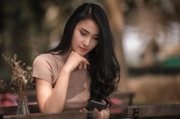 座っている美しいアジアの女性の女の子が公園で携帯電話でマッサージをチェックします。 Premium写真