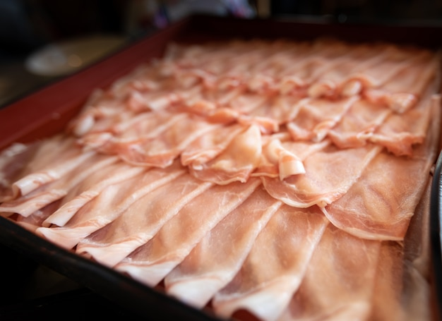 豚はレストラン日本のテーブルの上のコンテナー内の行にスライドします。 Premium写真