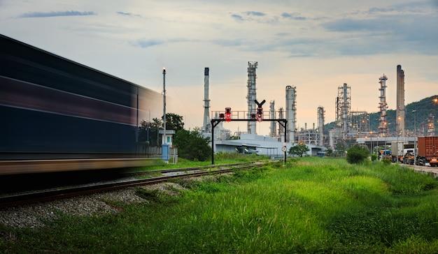 タイの列車が前景と夕方を移動する石油およびガス精製プラントの保管エリア Premium写真
