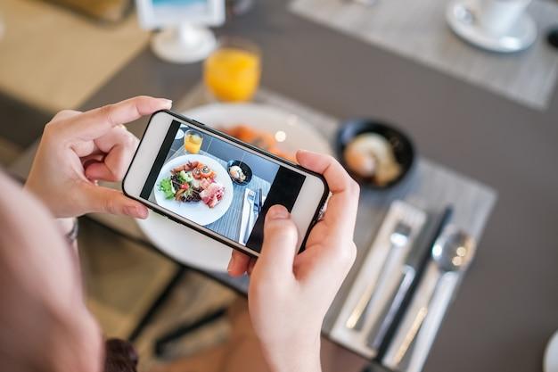 Девушка принимая фото еды с камерой телефона Premium Фотографии