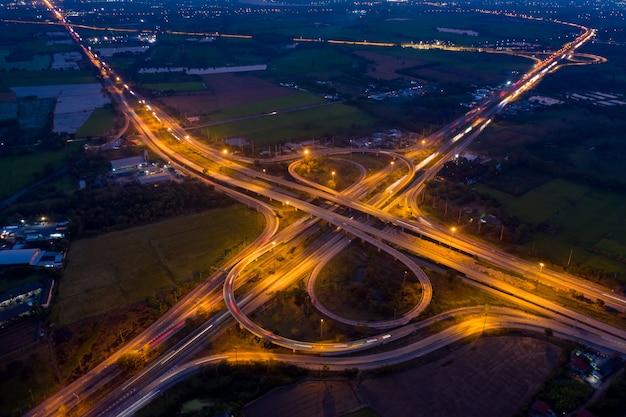 Аэрофотоснимок кольцевой дороги и развязки, связывающей город ночью Premium Фотографии