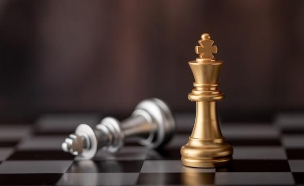 ゴールドキングに立って、チェス盤の上に落ちて Premium写真
