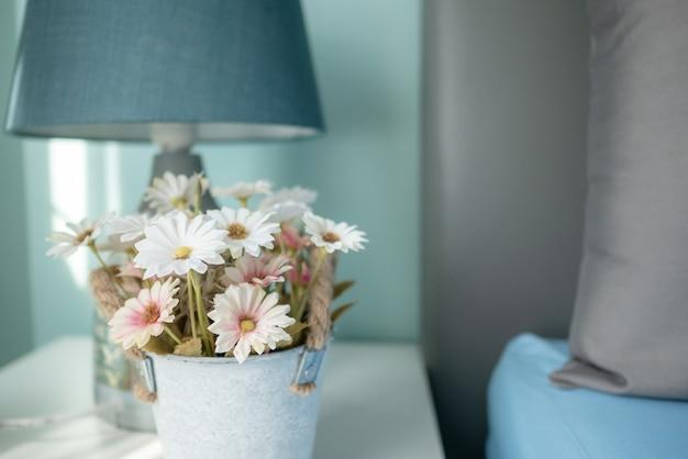 Размытые цветы и лампа на столе с солнечными лучами в спальне Premium Фотографии