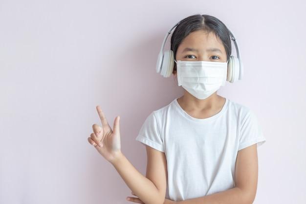 医療用防護マスクとヘッドフォンを身に着けているアジアの少女 Premium写真