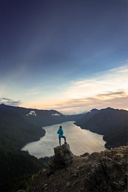 マウントストームキングオリンピック国立公園の頂上に立っている女性ハイカー Premium写真