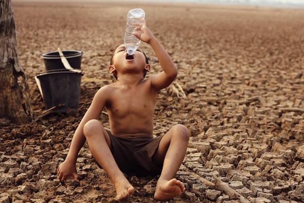 Азиатским мальчикам в настоящее время не хватает чистой воды для потребления. Premium Фотографии