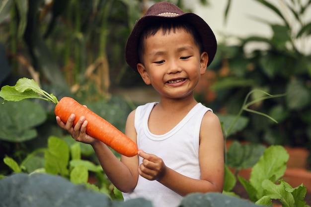 Азиатский мальчик в восторге от морковного продукта, который он посадил. концепции обучения вне класса Premium Фотографии