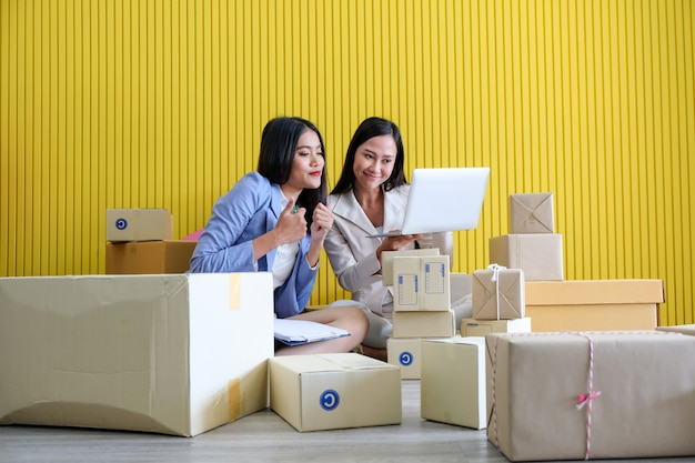 Красивая азиатская коммерсантка сидя с коробками вокруг ее. Premium Фотографии