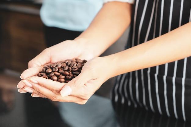 Сушеные коричневые кофейные зерна находятся в руках молодых сотрудников. Premium Фотографии