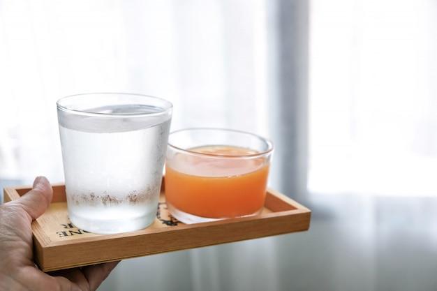 水とオレンジジュースは、身体をリフレッシュして癒すために飲むのに適した木製のトレイに入れられます。 Premium写真