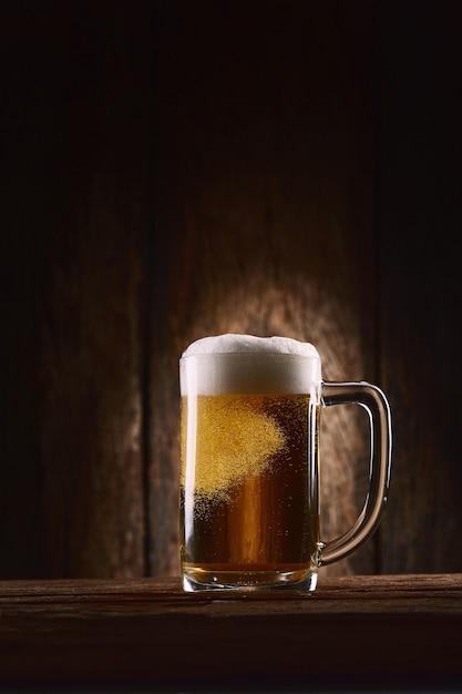 木製のテーブルの上のマグカップでビール Premium写真
