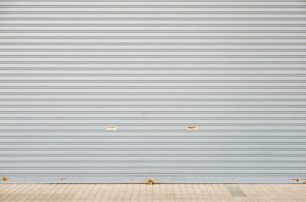 コンクリートタイル張りの床と大きなガレージ倉庫の入り口のローリングシャッタードア Premium写真