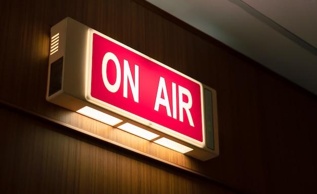 生放送ラジオ制作室の木製の壁に輝くオンエアサインアイコン Premium写真