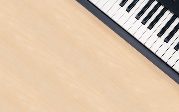 コピースペース、創造的なホームスタジオエンターテイメント機器、シンセサイザーキーを持つ木製のテーブル背景にミディキーボードピアノ Premium写真
