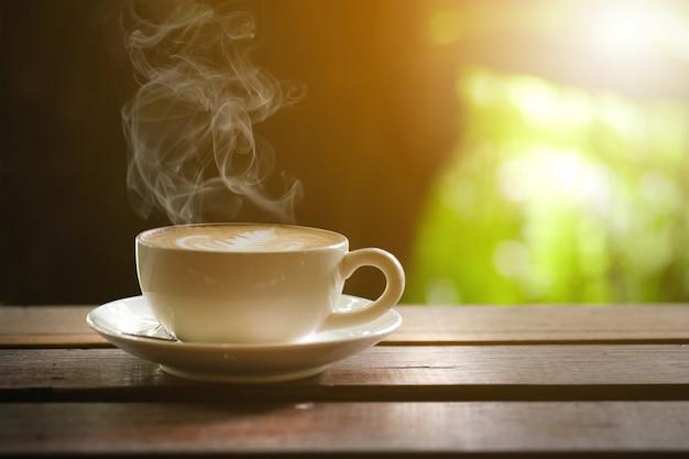 テラスの木製テーブルでホットコーヒー。 Premium写真