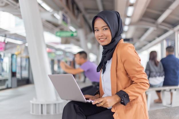 ノートパソコンでスカイトレインで働く美しい若いアジアの女の子。イスラム教徒の女性 Premium写真