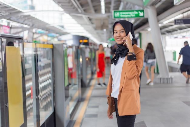 スカイトレイン駅で電話を使用して若いイスラム教徒の女性。 Premium写真