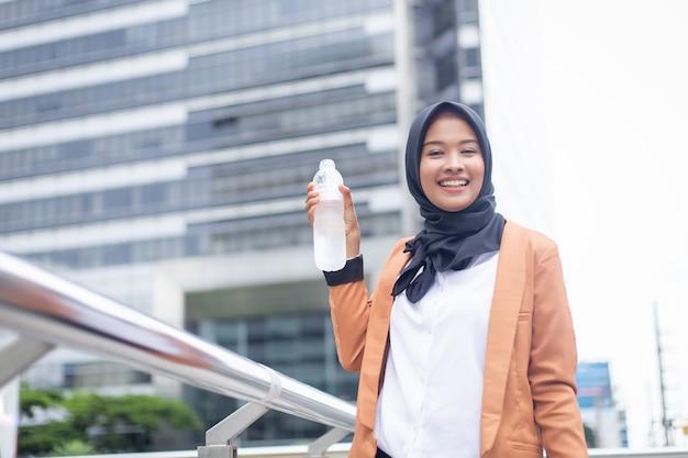 美しい若いアジアのイスラム教徒の飲料水。 Premium写真