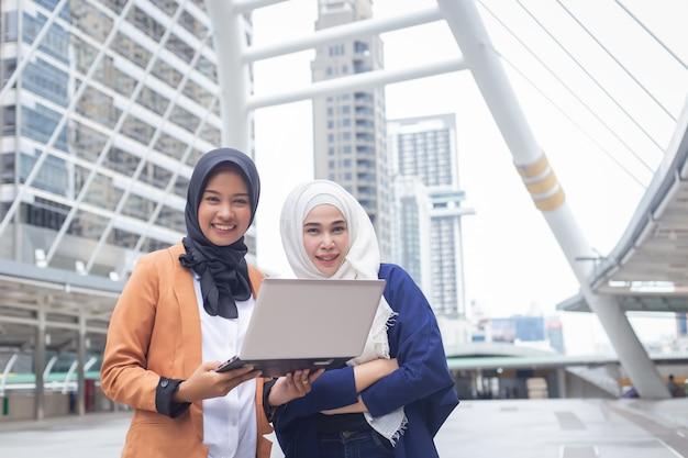 街のラップトップコンピューターで作業するイスラム教徒の実業家の笑みを浮かべてください。 Premium写真