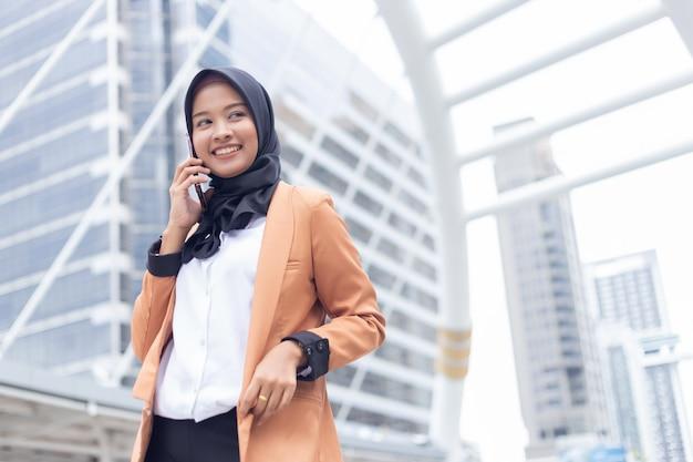 市内で電話を使用してビジネスのイスラム教徒の女性。 Premium写真