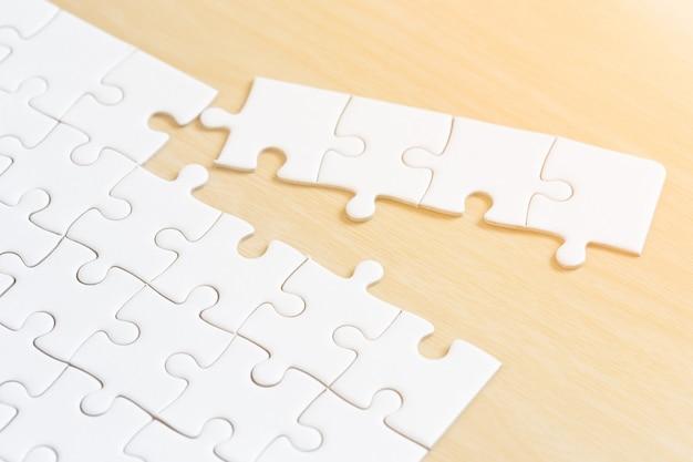 木製のテーブルに白い接続されたジグソーパズルのピース Premium写真