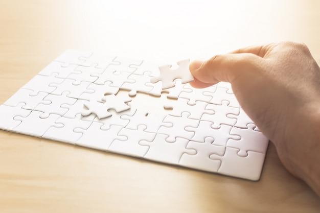 接続する男のジグソーパズルの手。 Premium写真