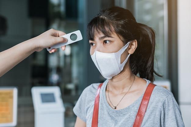 建物、コロナウイルス病医療概念に入る前にデジタル温度計訪問者のアジアの女性と発熱をチェックする役員。 Premium写真