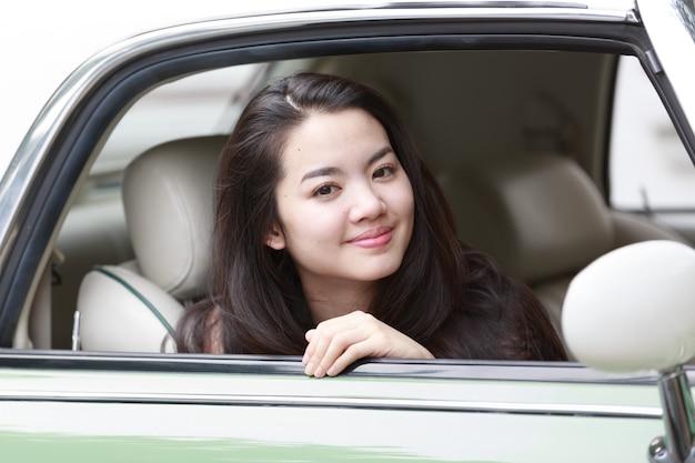 ビンテージ車の中で若いアジア女性 Premium写真