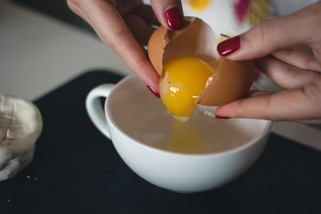 ベーキングのために卵を割る 無料写真