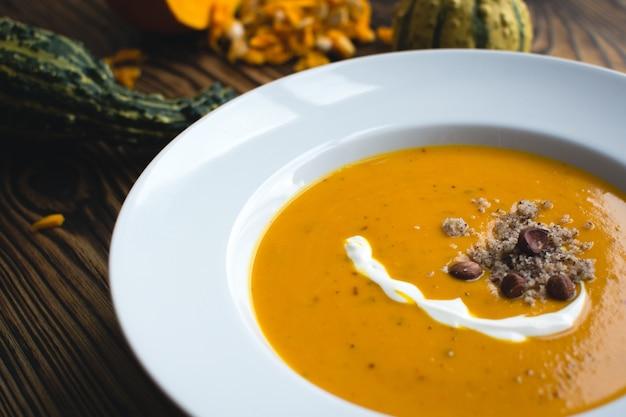 クリーミーなカボチャのスープ、クリームとヘーゼルナッツ 無料写真
