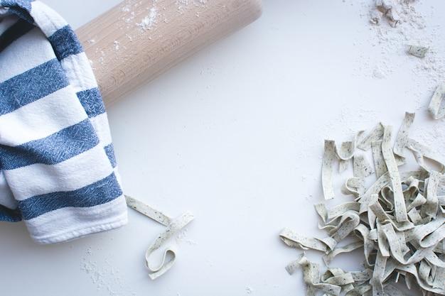 白い背景に木製のローラーで小麦粉で覆われたパスタ・タリアテッレ 無料写真