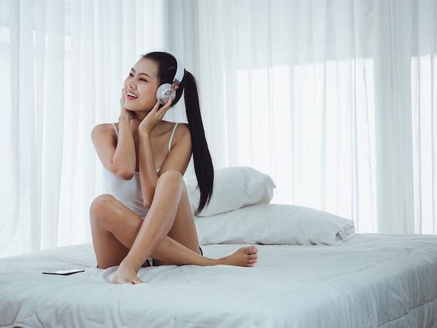 ベッドで音楽を聴くアジアの美しい女性 Premium写真