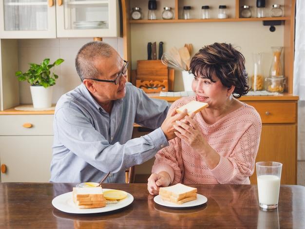 年配のカップルは朝食を一緒に食べています、男性は女性が食べるためにパンを入れます Premium写真
