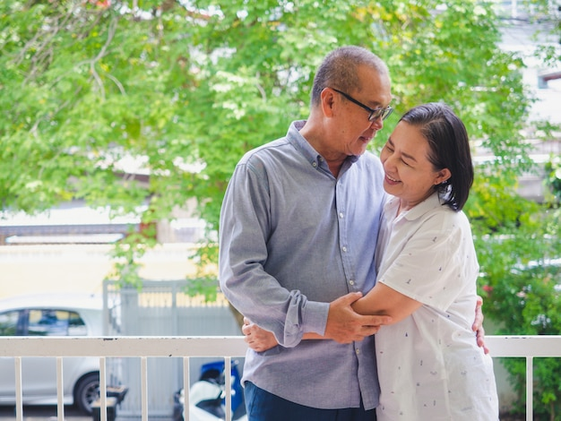 Старая пара обнималась на балконе Premium Фотографии