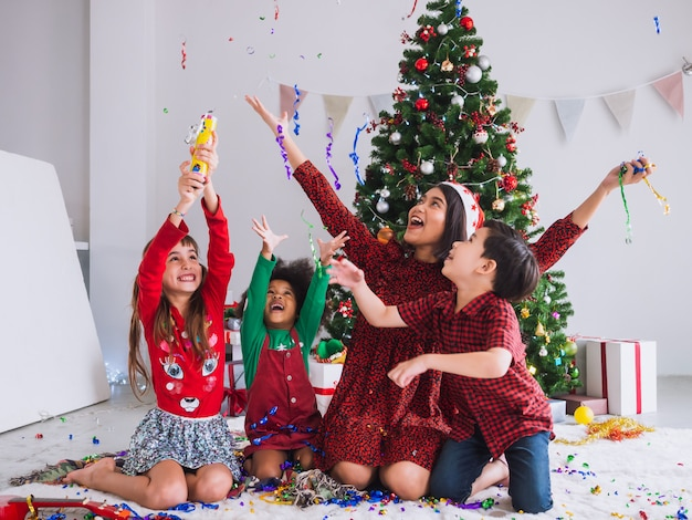 Мама и дети празднуют рождество и веселятся в доме с елкой Premium Фотографии