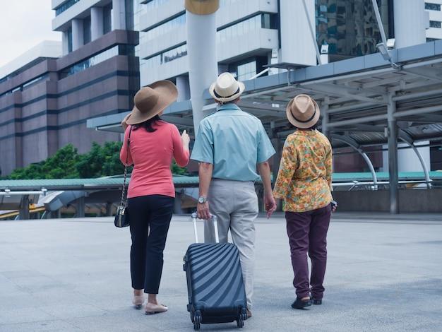 Группа пожилых людей путешествует по городу, пожилой мужчина и пожилая женщина смотрят и гуляют по городу Premium Фотографии