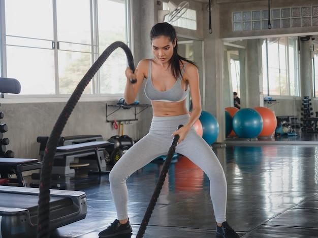 アジアの女性のジムでの戦いのロープ運動 Premium写真