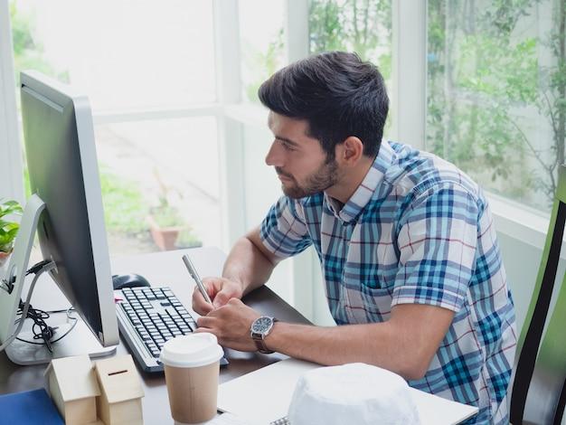 コーヒーと新聞で在宅勤務の若い男 Premium写真
