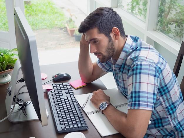 若い男が自宅で仕事と仕事について強調 Premium写真