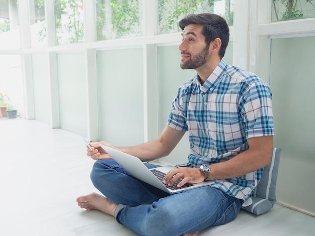 若い男が自宅でクレジットカードでオンラインショッピング Premium写真
