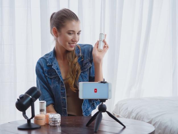 彼女の家でビジネスを行うコンピューターでオンラインで化粧品を売る女性 Premium写真