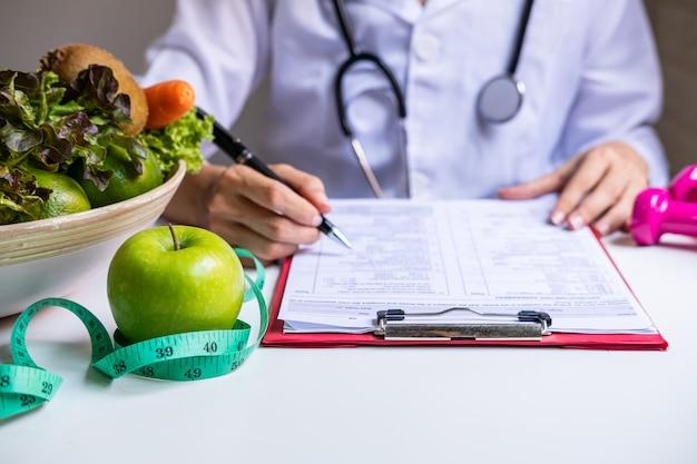 健康的な果物、野菜、測定テープ作業、正しい栄養と食事のコンセプトを持つ栄養士 Premium写真