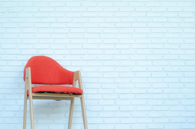 白いレンガの背景、モダンな部屋、コピースペースに赤い椅子。 Premium写真
